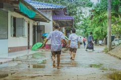 Students walk to the flood after rain. In school Royalty Free Stock Photography
