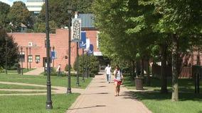 Students walking along walkway between University buildings stock video
