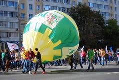 Students walking with big balloon Stock Image