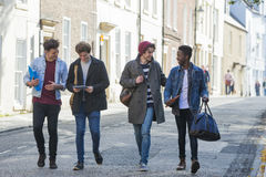 Students walking through the city. A happy group of male students smile and laugh as they walk through the city together. They are carrying their bags and books Royalty Free Stock Photos