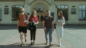 Students walking and communicating in campus. Group of joyful college students with backpacks and textbooks walking and communicating in university campus after stock video footage