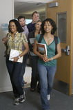 Students Walking Out Of Classroom. Group of multiethnic students walking out of classroom royalty free stock photos
