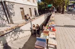 Students walking from the subway with outdoor market of second hand books royalty free stock photo