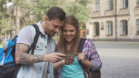 Students watch images on smartphone on campus. Cute young students watching images on smartphone on campus. Handsome brunette men holding cellphone in his hands royalty free stock images