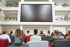 Students watching big screen in university atrium, back view Royalty Free Stock Image