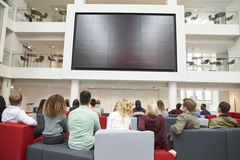 Students watching big screen in university atrium, back view Royalty Free Stock Photography