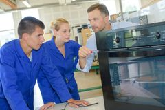 Students watching man with kitchen appliance. Students watching men with kitchen appliance student stock photography
