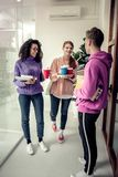 Students wearing casual clothes having coffee break between classes. Break between classes. Three students wearing casual nice clothes having coffee break stock photos