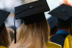 Students wearing gowns and hats sitting indoors, waiting to receive diplomas, graduation day in university, college commencement royalty free stock images
