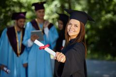 Students wearing graduation gowns and caps Stock Photos