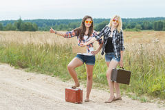 Students wearing sunglasses hitchhike on road Stock Image