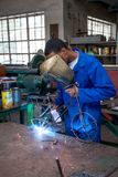 Students welding in a workshop. Johannesburg, South Africa, March 7 - 2018: Students welding in a workshop. Boy welding a bike out of metal wire Royalty Free Stock Image
