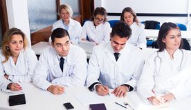 Students in white coats listen to lecture. In audience royalty free stock photos