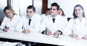 Students in white coats listen to lecture. In audience stock photography
