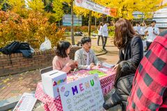 Students of Woosong College sell food tickets. Daejeon, South Korea-November, 8,2017: Students of Woosong College sell food tickets to attendees at Woojeong royalty free stock image
