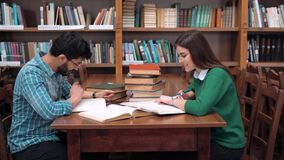 Students Work on Home Assignment. Two smart students working on home assignment, reading books attentively, sitting at square library table next to the stock video