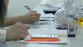 Students at work in the laboratory of chemistry take notes in a notebook. Female Pupil Using phone In Science Lesson Stock Photos