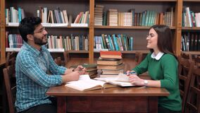 Students Work in Pair. Two lovely students working in pair, talking about read material with pleasure, good-looking bearded boy and beautiful brunette sitting at stock video