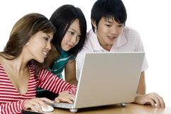 Students Working As Group. Three young asian adults working on a laptop computer royalty free stock photography