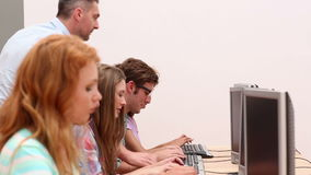 Students working in computer room with lecturer stock video footage