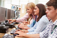 Students Working At Computers In Library With Teacher Royalty Free Stock Photography