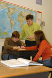 Students Working Together in Class. A teacher helps two students working together in classroom Royalty Free Stock Images