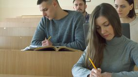Students write in their exercise books. Young students writing in their exercise books at the lecture hall. Caucasian undergraduates looking at the lecturer Stock Image