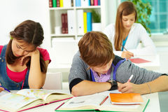 Students writing. Portrait of smart guy making notes in copybook with his classmates near by Stock Photography