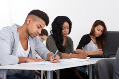 Students Writing At Desk Stock Images