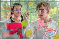 Students writing mathematics fomulars on a glass board. Caucasian and Asian teenage students writing mathematics fomulars on a glass board