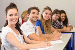 Students writing notes in classroom. Portrait of students writing notes in classroom Royalty Free Stock Photos