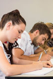 Students writing notes in classroom Stock Photo