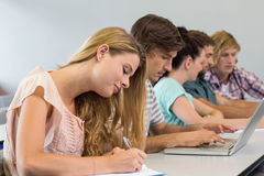 Students writing notes in classroom. Side view of students writing notes in classroom Royalty Free Stock Photo
