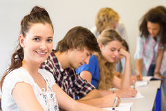 Students writing notes in classroom Royalty Free Stock Images