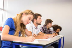 Students writing notes in classroom. Side view of students writing notes in classroom Royalty Free Stock Images