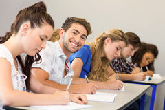 Students writing notes in classroom. Side view of students writing notes in classroom Stock Photos