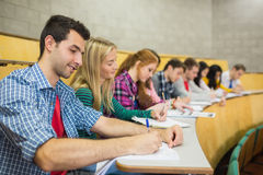 Students writing notes in a row at lecture hall Stock Images