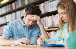 Students writing to notebooks in library Stock Images
