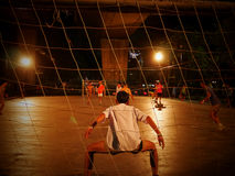 Students and young adults play soccer at night in Bangkok, Royalty Free Stock Image