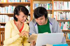 Students in library are a learning group. Students - Young Asian women and men in library with laptop and book learn, they are a learning group Royalty Free Stock Photography