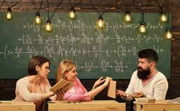 Students, young scientists studying, holds book , while professor teaches, explains, chalkboard background Girls. Students and bearded teacher, lecturer stock photos