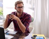 Studentsammanträde på ett skrivbord med kaffe i hans händer Fotografering för Bildbyråer