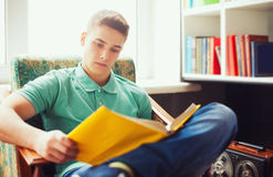 Studentsammanträde på stol och läseboken Arkivfoton