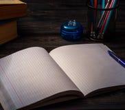 Studentskolaskrivbord med den öppna anteckningsboken för mellanrum Royaltyfri Bild