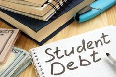 Studentskuldtecken p? en sida och pengar arkivbilder