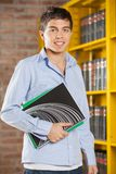 StudentSmiling While Holding böcker i högskola Royaltyfri Fotografi