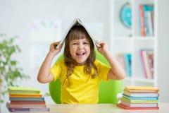 Studentunge med en bok över hennes huvud arkivfoton