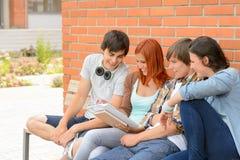 Studentvänner som tillsammans studerar den utvändiga universitetsområdet Fotografering för Bildbyråer