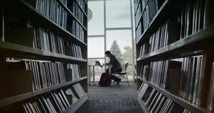 Studentzitting in bibliotheek, lezingsboek stock footage