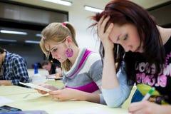 Studentzitting in een klaslokaal Royalty-vrije Stock Afbeeldingen
